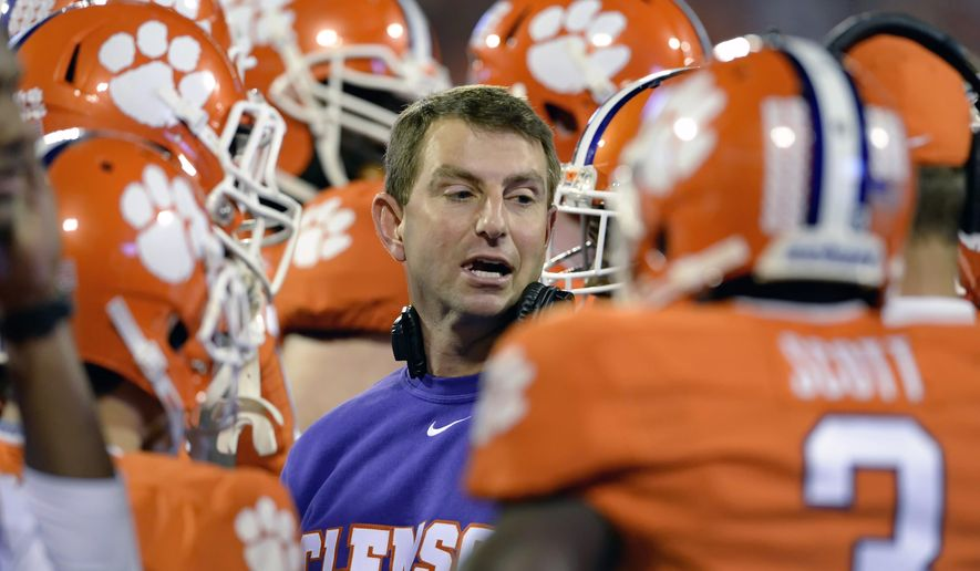 In this Oct. 25, 2014, file photo, Clemson coach Dabo Swinney talks to his team during an NCAA college football game against Syracuse in Clemson, S.C. (AP Photo/ Richard Shiro) ** FILE **