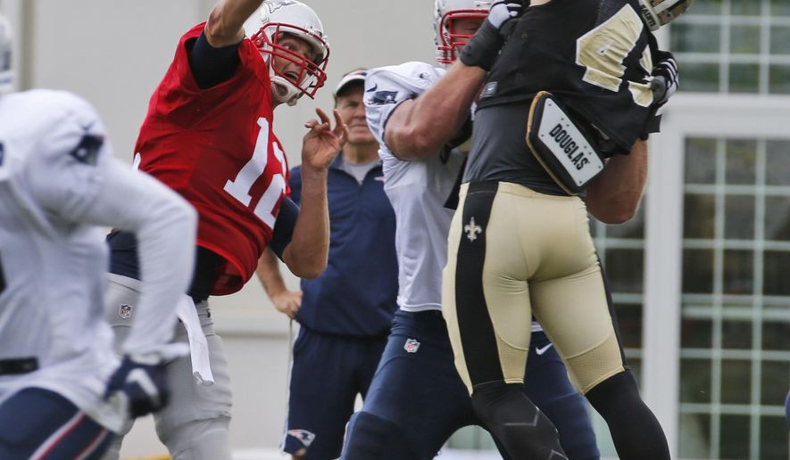 New England Patriots quarterback Tom Brady (12) tosses a pass over New Orleans Saints safety Vinnie Sunseri, right, during a joint practice between the Patriots and New Orleans Saints at the Saint's NFL football training camp in White Sulphur Springs, W.Va., Thursday, Aug. 20, 2015.  (AP Photo/Steve Helber)