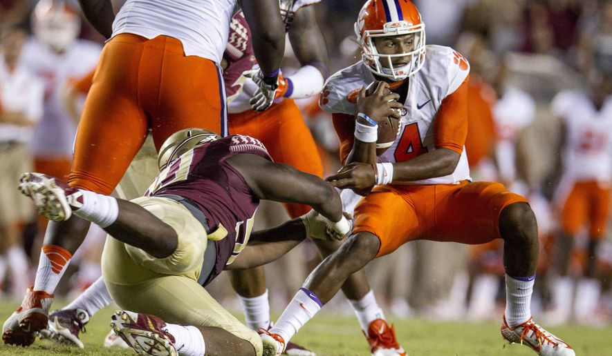 """FILE - In this Sept. 20, 2014, file photo, Clemson quarterback Deshaun Watson, right, escapes a sack from Florida State defensive tackle Eddie Goldman during an NCAA college football game in Tallahassee, Fla. There's only one issue anyone wants to talk about when it comes to the Tigers: Can quarterback Deshaun Watson stay healthy.Watson, the smiling, friendly sophomore, said he will hear that question a dozen or so times a day from students, fans and others. He responds the same way, """"I'm ready to go."""" (AP Photo/Mark Wallheiser, File)"""