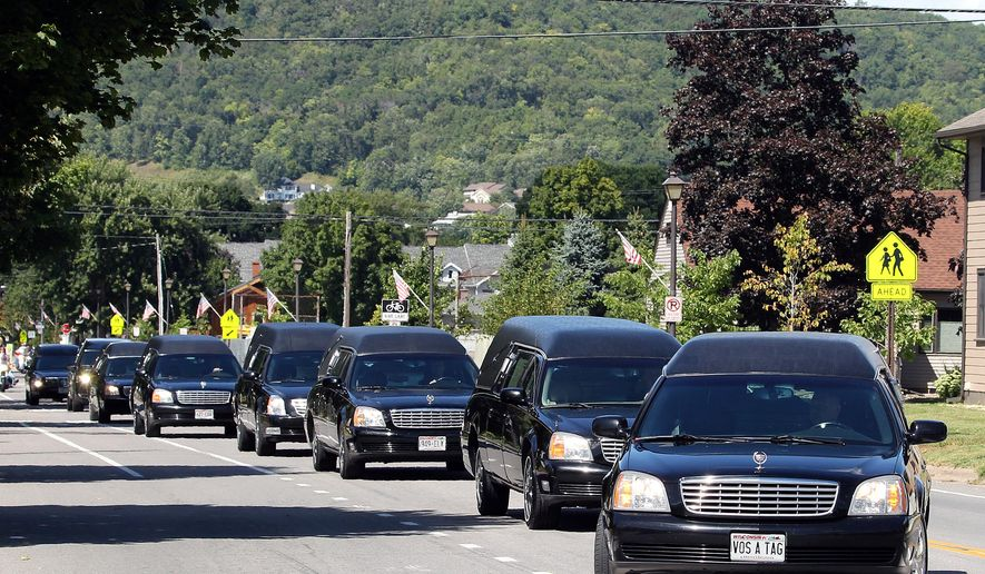 Eight hearses carrying the family members killed in the Aug. 8, shooting in Houston, Texas, travel from United Methodist Church in La Crescent, Minn., to Prince of Peace Cemetery on Thursday, Aug. 20, 2015. David Conley faces capital murder charges for the killings. Authorities say he handcuffed most of the family members and eventually shot each in the head. (Rory O'Driscoll/La Crosse Tribune via AP) MANDATORY CREDIT