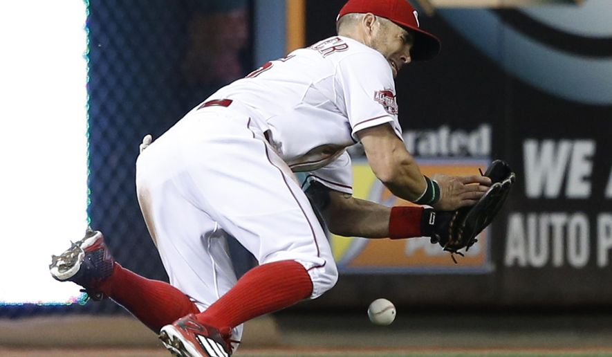 Cincinnati Reds left fielder Skip Schumaker can't retrieve the ball hit by Arizona Diamondbacks A.J. Pollock during the seventh inning of a baseball game, Thursday, Aug. 20, 2015, in Cincinnati. (AP Photo/Gary Landers)