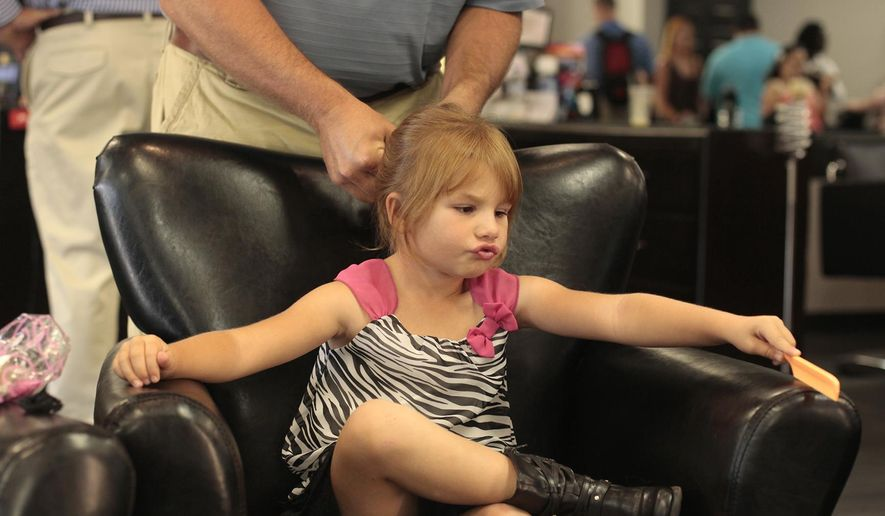 In this photo taken Thursday, Aug. 13, 2015, Tatum Lynn, 4, has a braid put in her hair by her father Colin Lynn during the Dads and Daughters Date Night at Siren Salon in Gillette, Wyo. (Tim Goessman/Gillette News Record via AP) TV OUT; MANDATORY CREDIT