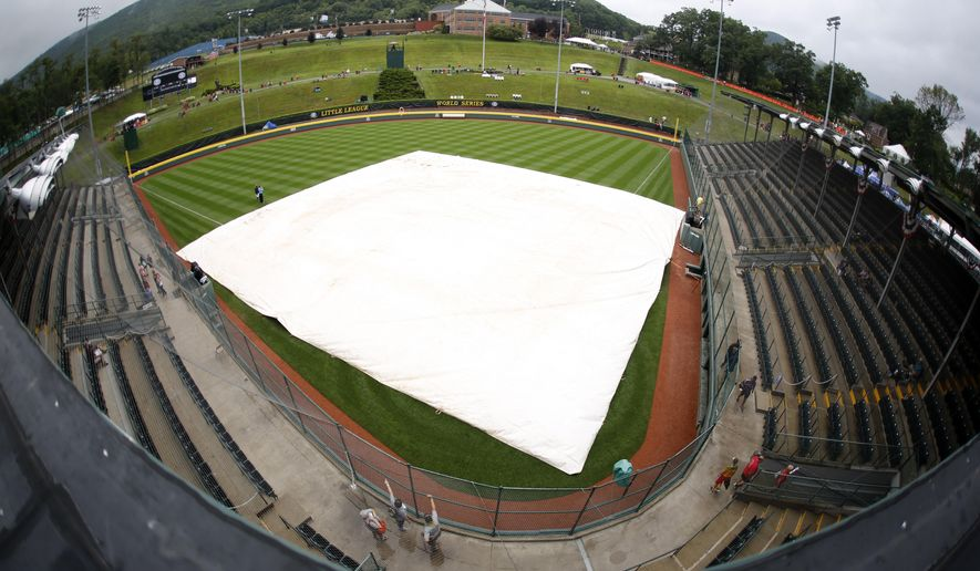 Rain falls on the covered field at Lamade Stadium Thursday, Aug. 20, 2015, in South Williamsport, Pa. The opening ceremony and the first day of four games of the Little League World Series tournament has been postponed due to rain. The tournament will resume play on Friday with eight games being played. (AP Photo/Gene J. Puskar)