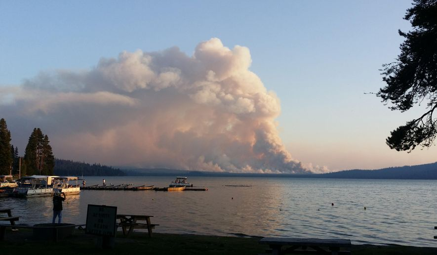 In this photo taken Wednesday, Aug. 19, 2015, smoke from the National Creek Complex fire rises above the horizon across Diamond Lake, Ore., in this view from the Diamond Lake Resort. The wildfire, located between Diamond Lake and Crater Lake in southern Oregon, has forced the closure of the north entrance to Crater Lake, but other parts of Crater Lake Park National Park remain open and the Diamond Lake Resort is still in operation. (AP Photo/John H. Jonesburg III) MANDATORY CREDIT
