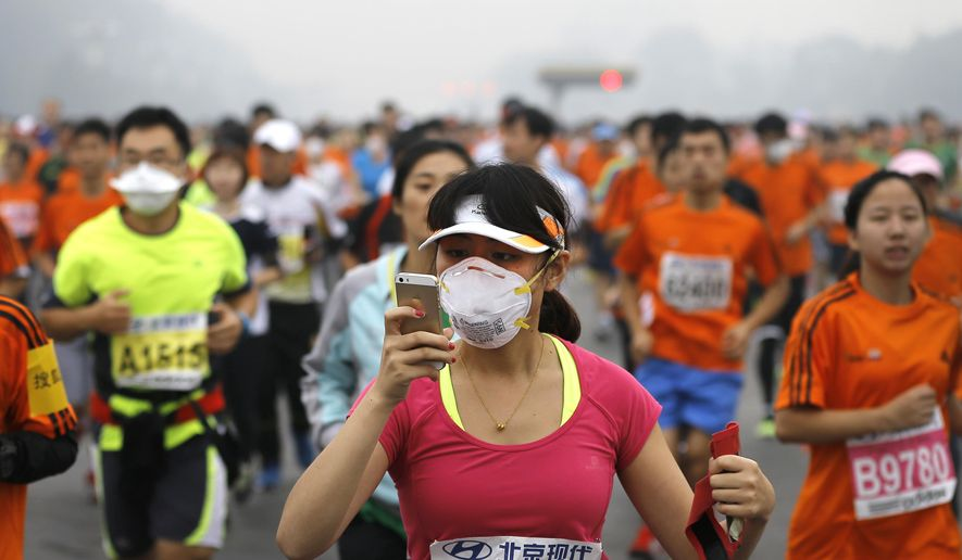 FILE - In this Oct. 19, 2014, file photo, a runner, wearing a mask to protect herself from pollutants, looks at her smartphone as she and others jog past Chang'an Avenue near Tiananmen Square shrouded in haze at the start of 2014 Beijing International Marathon in Beijing. Seven years after the 2008 Beijing Olympics sparked talk of a dramatic clean-up of pollution in Beijing, a milky haze still covers the city on most days and is expected to be there when the IAAF World Championships marathons take place - Aug. 29, 2015 for the men, and Aug. 30, 2015 for the women. According to a recent study, 1.6 million people die each year in China from heart, lung and stroke-related problems due to polluted air. (AP Photo/Andy Wong, File)