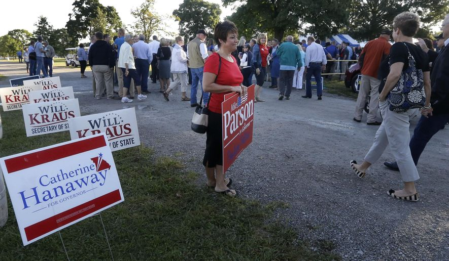 Chele Trammel holds election signs outside the Governor's Ham Breakfast at the Missouri State Fair in Sedalia, Mo., Thursday, Aug. 20, 2015. (AP Photo/Orlin Wagner)