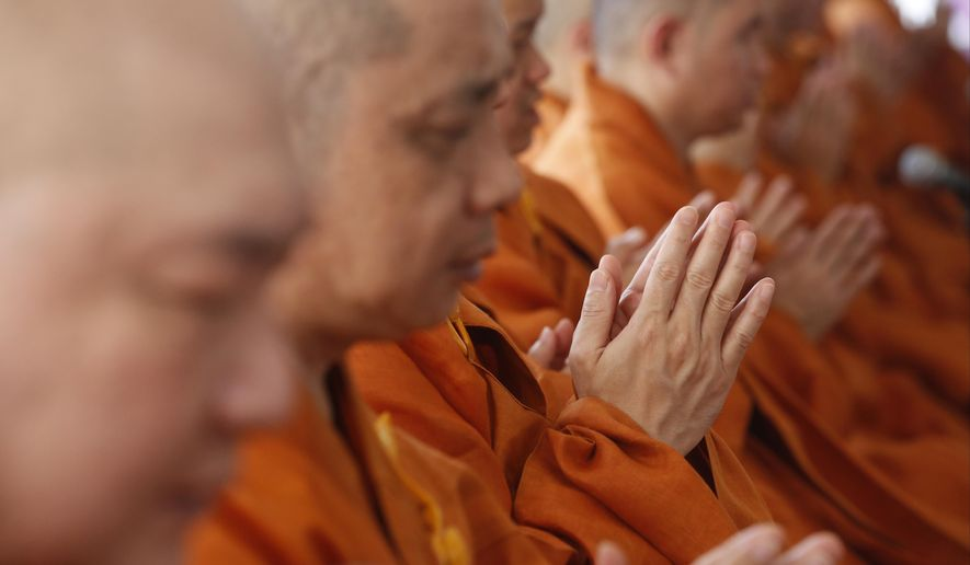 Buddhist monks pray at a religious ceremony for bombing victims at a plaza across from the Erawan Shrine at Rajprasong intersection, the scene of Monday's bombing, in Bangkok, Thailand, Friday, Aug. 21, 2015. Religious ceremonies were held to honor the victims of the deadly bombing at a Bangkok shrine four days ago.(AP Photo/Sakchai Lalit)