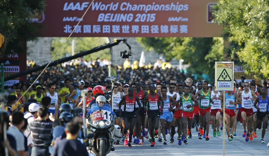 Competitors start the men's marathon at the World Athletic Championships in Beijing, Saturday, Aug. 22, 2015. (AP Photo/Mark Schiefelbein)