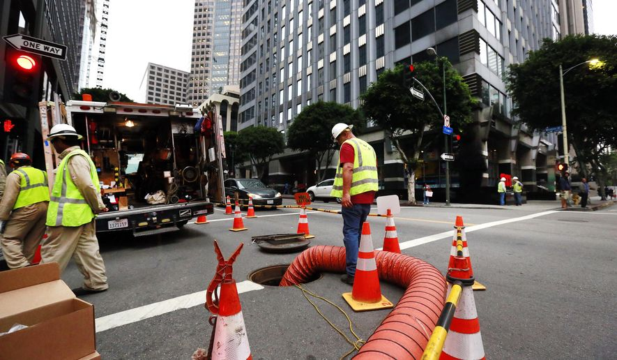 A city utility crew work in response to an electrical equipment explosion, Friday, Aug. 21, 2015, in downtown Los Angeles. The explosion shook a 19-story downtown  office building, sending two people to the hospital and leaving a dozen surrounding buildings without power Friday. (AP Photo/Nick Ut)