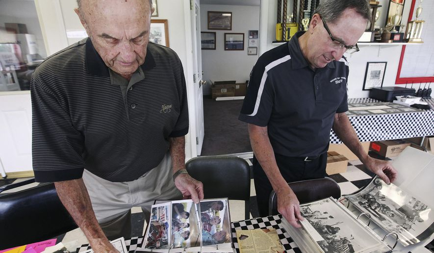 In this July 1, 2015, photo, Gus Traeder, 89, left, and his son, Terry, look over photo albums containing decades of local karting history at their office at TNT Kartways in West Quincy, Mo. Gus Traeder has been a karting legend for almost 60 years. He is stepping back from the sport he helped develop in this region. (Steve Bohnstedt/The Quincy Herald-Whig via AP) MANDATORY CREDIT