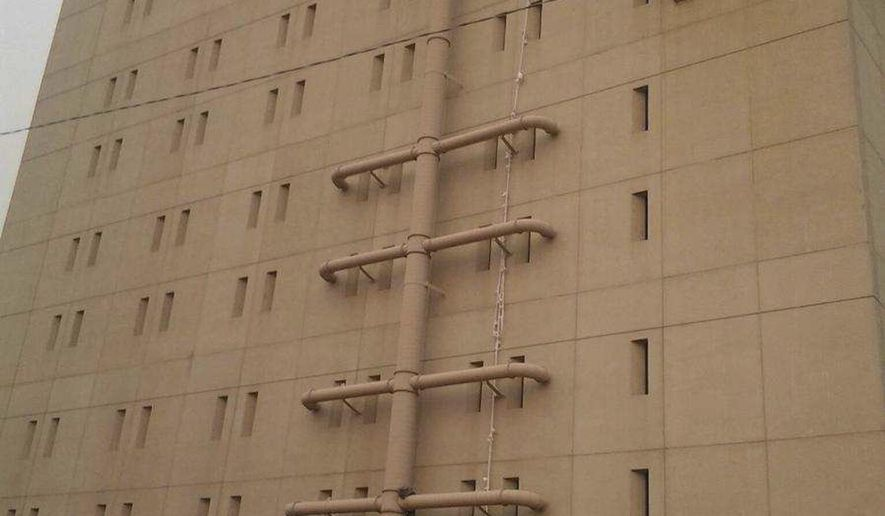 In this image made from video taken, Thursday, Aug. 20, 2015, bed sheets used in an apparent escape attempt are seen hanging from a top floor window of the Spokane County Jail reaching all the way to the ground in Spokane, Wash. Staffers at the jail in eastern Washington state foiled the escape attempt by spotting the long trail of knotted bed sheets hanging from the window of a cell housing a suspect in a murder-for-hire plot. They saw the rope of sheets that nearly reached the ground around 4:30 a.m. Thursday and put the jail on lockdown. (Reed Schmitt/KHQ via AP) MANDATORY CREDIT