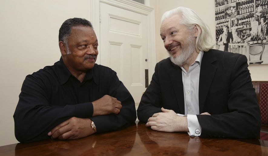WikiLeaks founder Julian Assange, right, sits with Reverend Jesse Jackson of USA, inside the Embassy of Ecuador in London, Friday Aug. 21, 2015. Assange has been holed up inside the Ecuador Embassy building since 2012, as he fights against extradition to Sweden in relation to allegations of sexual assault. (Yui Mok  / PA via AP) UNITED KINGDOM OUT - NO SALES - NO ARCHIVES