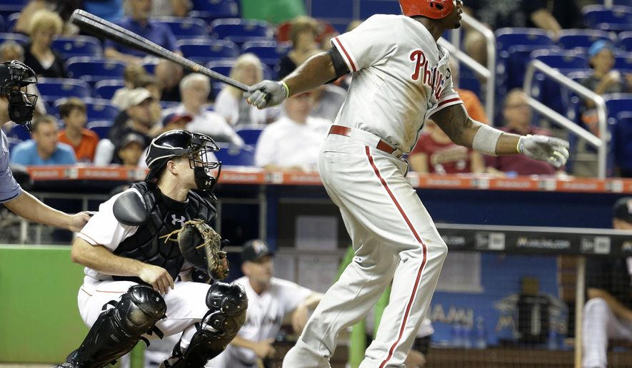 Philadelphia Phillies' Ryan Howard, right, watches after hitting a double as Miami Marlins catcher J.T. Realmuto, left, looks on in the fourth inning of a baseball game, Friday, Aug. 21, 2015, in Miami. The Phillies defeated the Marlins 7-1. (AP Photo/Lynne Sladky)