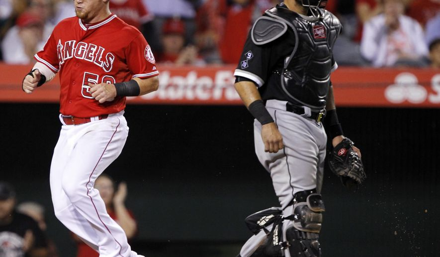 Los Angeles Angels' Kole Calhoun, left, scores without a throw to Chicago White Sox catcher Geovany Soto, on an RBI single by designated hitter Albert Pujols during the fifth inning of a baseball game in Anaheim, Calif., Thursday, Aug. 20, 2015. (AP Photo/Alex Gallardo)