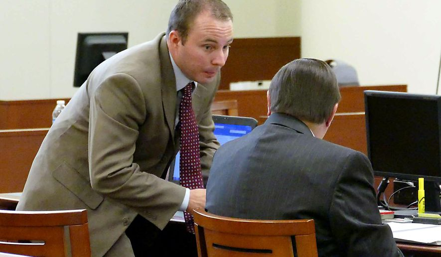 Police officer Randall Kerrick, left, talks with his attorney George Laughrun at the Mecklenburg County Courthouse in Charlotte, N.C. Friday, Aug. 21, 2015. Kerrick faces voluntary manslaughter charges in the shooting death of an unarmed black man seeking help after a September 2013 car crash. (Davie Hinshaw /The Charlotte Observer via AP, Pool)