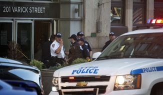 Police gather outside a federal building following a shooting Friday, Aug. 21, 2015, in New York. Police said a man walked into the building and opened fire before shooting himself. (AP Photo/Bebeto Matthews)