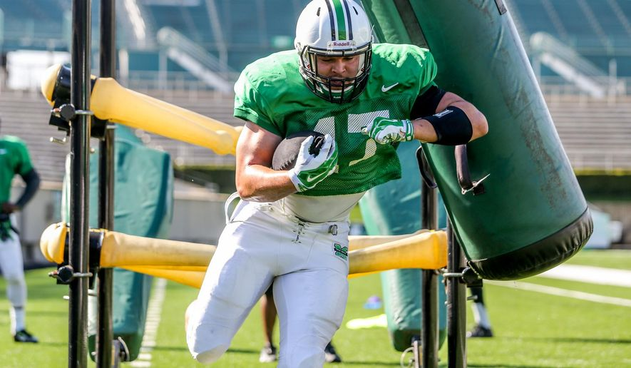 FILE - In this April 18, 2015, file photo, Marshall running back Devon Johnson runs through a drill as the NCAA college football team held an intrasquad scrimmage in Huntington, W.Va. Nicknamed Rockhead for his bruising style, the 244-pound Johnson's move to the backfield a year ago from backup tight end was intended to provide protection for the quarterback. (Sholten Singer/The Herald-Dispatch via AP, File)