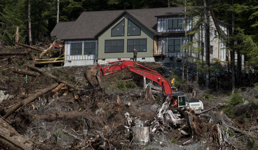 Sitka City Administrator Mark Gorman stands in front of a house on Kramer Avenue as contractors and other search members look in the area where city building inspector William Stortz was last seen Tuesday when a landslide hit, in Sitka, Alaska, Thursday, August 20, 2015. Bodies of two of three victims of Tuesday's landslide were recovered Thursday. (James Poulson/Daily Sitka Sentinel via AP)