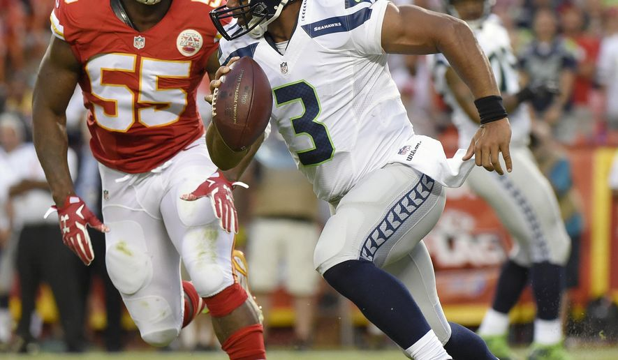 Seattle Seahawks quarterback Russell Wilson (3) scrambles from Kansas City Chiefs linebacker Dee Ford (55) during the first half of an NFL football game at Arrowhead Stadium in Kansas City, Mo., Friday, Aug. 21, 2015. (AP Photo/Ed Zurga)