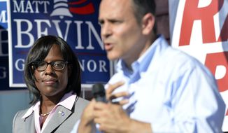 Then-Kentucky Republican Lt. Gubernatorial candidate Jenean Hampton, left, looks on as her running mate, Gubernatorial candidate Matt Bevin, addresses their supporters from the steps of the Bevin campaign headquarters in Somerset Ky., Friday, Aug. 21, 2015. (AP Photo/Timothy D. Easley)