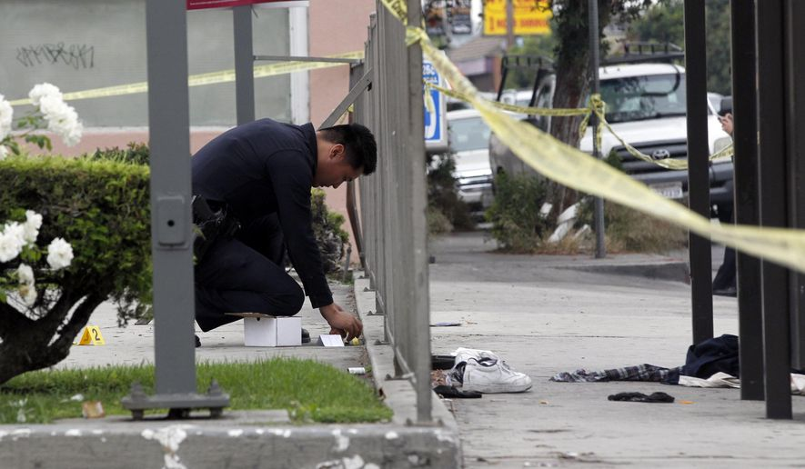 A Los Angeles Police officer investigates the scene of a shooting on a street where multiple shootings took place in the West Adams neighborhood of Los Angeles,  Friday, Aug. 21, 2015. Detective Joe Chavez says a man was shot at a bus stop and two other victims, male and female, were shot in a nearby alley. Chavez had no immediate information on the circumstances or motive. (AP Photo/Nick Ut)