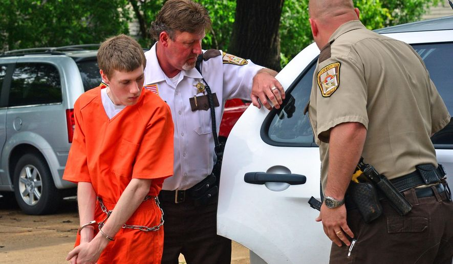 In this photo taken June 18, 2014, John LaDue, accused of planning an attack on his school, is escorted by Waseca County Sheriff's  Deputies for a hearing in Waseca, Minn. District Judge Robert Birnbaum on Friday, Aug. 21, 2015, has certified the Waseca teenager, accused of planning to kill his family and attack his high school, to stand trial as an adult. (Richard Sennott/Star Tribune via AP)  MANDATORY CREDIT; ST. PAUL PIONEER PRESS OUT; MAGS OUT; TWIN CITIES LOCAL TELEVISION OUT