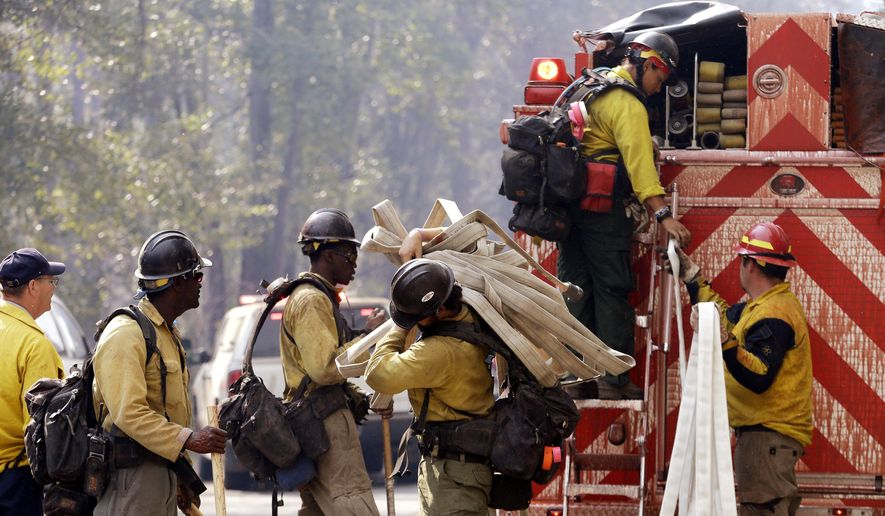 "Firefighters line up to get gear out of the back of a fire truck as they get ready to head out onto a line Thursday, Aug. 20, 2015, in Twisp, Wash. Authorities say three firefighters died after their vehicle crashed and was apparently caught by a ""hellstorm"" of flames as they battled a blaze in the state. (AP Photo/Elaine Thompson)"