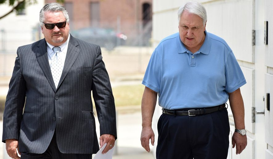 Former state Sen. Irb Benjamin, 68, of Madison, right, walks to the federal courthouse in downtown Jackson, Miss., Friday, Aug. 21, 2015 with attorney Joe Hollomon for a hearing on federal charges that he paid bribes and kickbacks to a former Mississippi corrections commissioner in exchange for contracts. Benjamin pleaded not guilty to three counts of conspiracy and bribery. He was released on $10,000 bond. (Rick Guy/The Clarion-Ledger, via AP)