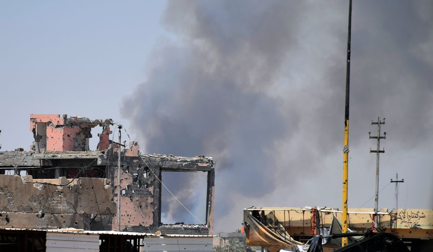 Smoke rises above a damaged building following a U.S.-led coalition airstrike against Islamic State group positions during a military operation to regain control of the eastern suburbs of Ramadi, in Anbar province, Iraq, on Aug. 15, 2015. (Associated Press) **FILE**