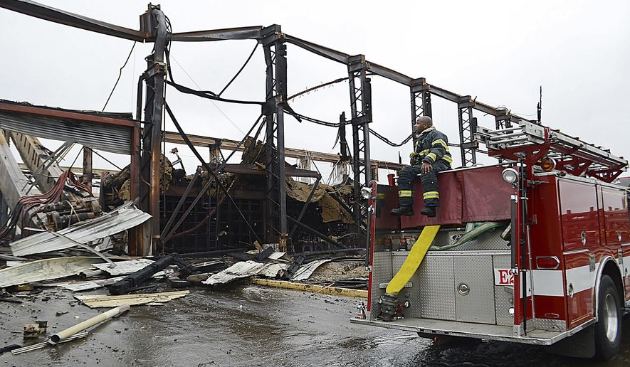 Firefighter Vaughn Hardiman looks at the aftermath of a huge three-alarm fire that destroyed the Alco Metal and Iron Company on Mare Island, Friday, Aug. 21, 2015, in Vallejo, Calif. A fast-moving warehouse fire at a former San Francisco Bay Area Navy shipyard lit up the night sky, but caused no injuries. The fire broke out shortly before midnight Thursday at the recycling yard. Residents were being asked to avoid the area Friday, but an official shelter-in-place advisory was not issued. (Chris Riley/Vallejo Times-Herald via AP)