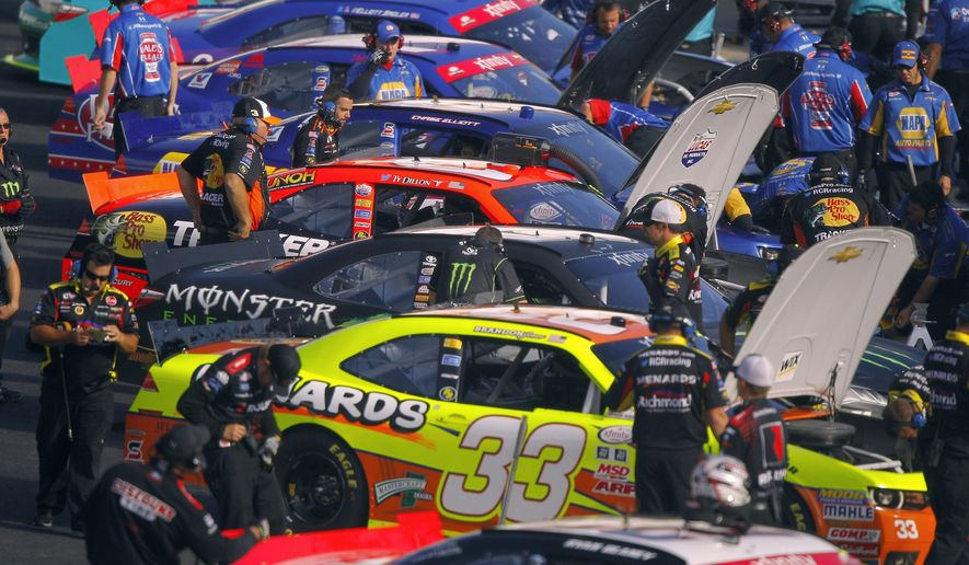 Crew members work on cars during practice for the Food City 300 NASCAR Xfinity Series auto race on Friday, Aug. 21, 2015, in Bristol, Tenn. (AP Photo/Wade Payne)