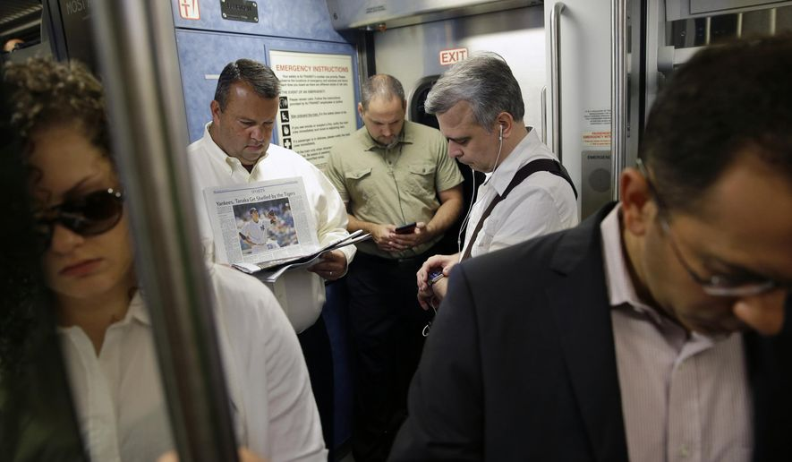 FILE- In this June 22, 2015 file photo, commuters read and check their phones as they wait for a New Jersey Transit passenger train to start its trip to New York from Trenton, N.J. Delays this summer on trains between New York and New Jersey have been so bad lately that federal, state and city officials have begun talking with new urgency about long-stalled plans to build a second set of tunnels. (AP Photo/Mel Evans, File)