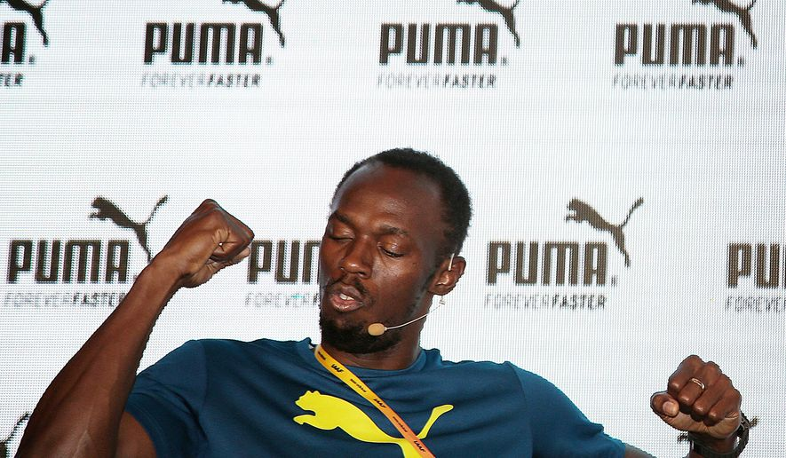 Jamaican sprinter Usain Bolt flexes his muscles jokingly while responding to a question from members of the media during a press conference, Thursday, Aug. 20, 2015, in Beijing, China. Bolt will be competing in the upcoming World Athletics Championships in Beijing, where he will look to retain his Men's 100 meter and 200 meter world titles. (AP Photo/Wong Maye-E)