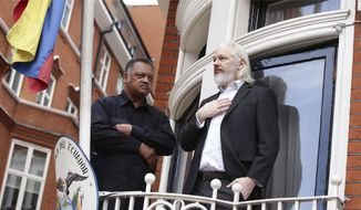 WikiLeaks founder Julian Assange, right, sits with Reverend Jesse Jackson of USA, stand on the balcony of the Embassy of Ecuador in central London, Friday Aug. 21, 2015. Assange has been holed up inside the Ecuador Embassy building since 2012, as he fights against extradition to Sweden in relation to allegations of sexual assault. (Yui Mok/PA via AP) ** FILE **