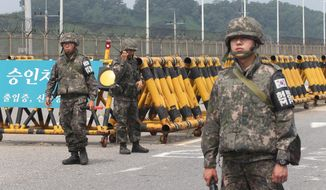 South Korean army soldiers stand guard at Unification Bridge near the border village of Panmunom in Paju, South Korea, Friday, Aug. 21, 2015. South Korea fired dozens of shells Thursday at rival North Korea after the North lobbed several rounds across the world's most heavily armed border and threatened to take further action unless Seoul ends its loudspeaker broadcasts. The North denied it fired any shots and warned of retaliation for what it called a serious provocation. (AP Photo/Ahn Young-joon)