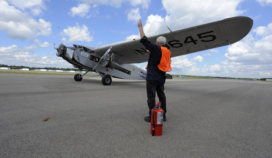 In this photo taken on Thursday, Aug. 20, 2015, volunteer Bruce Breisch of Livonia signals pilot John Maxfield as he begins to taxi in a vintage Ford Tri-Motor plane at Oakland County International Airport in Waterford, Mich.  The Oakland County International Airport's 30th annual Open House & Air Show takes place this weekend. (Steve Perez /Detroit News via AP)  DETROIT FREE PRESS OUT; HUFFINGTON POST OUT; MANDATORY CREDIT