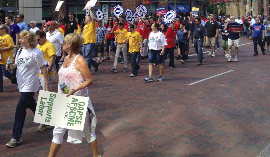 Hundreds of union workers and their supporters demonstrated and marched in downtown Columbus, Ohio, Friday Aug. 21, 2015, to protest the politics of billionaire industrialists Charles and David Koch and their flagship conservative organization, Americans for Prosperity. (AP Photo/Julie Smyth)