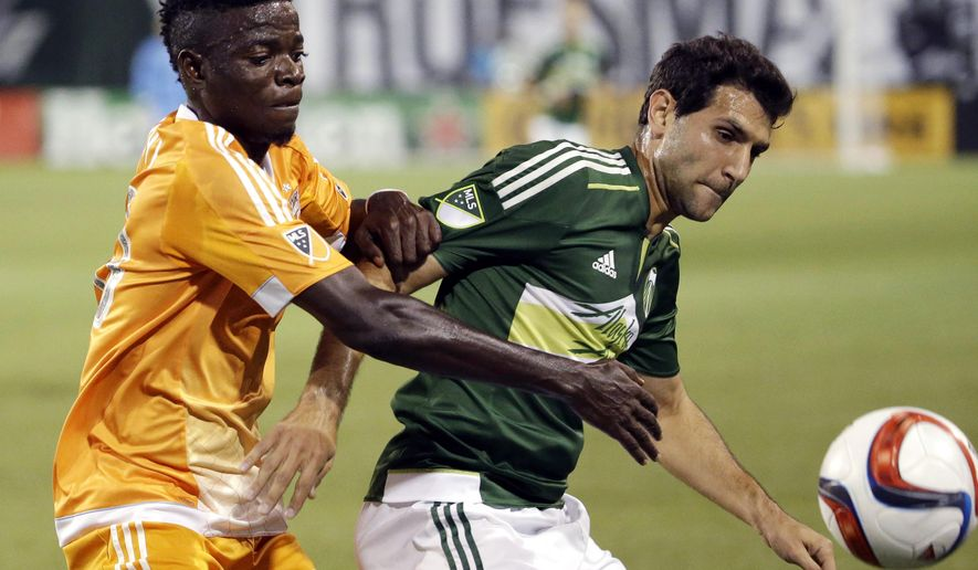 Houston Dynamo midfielder Rasheed Olabiyi, left, fights for the ball with Portland Timbers midfielder Diego Valeri during the first half of an MLS soccer game in Portland, Ore., Friday, Aug. 21, 2015. (AP Photo/Don Ryan)