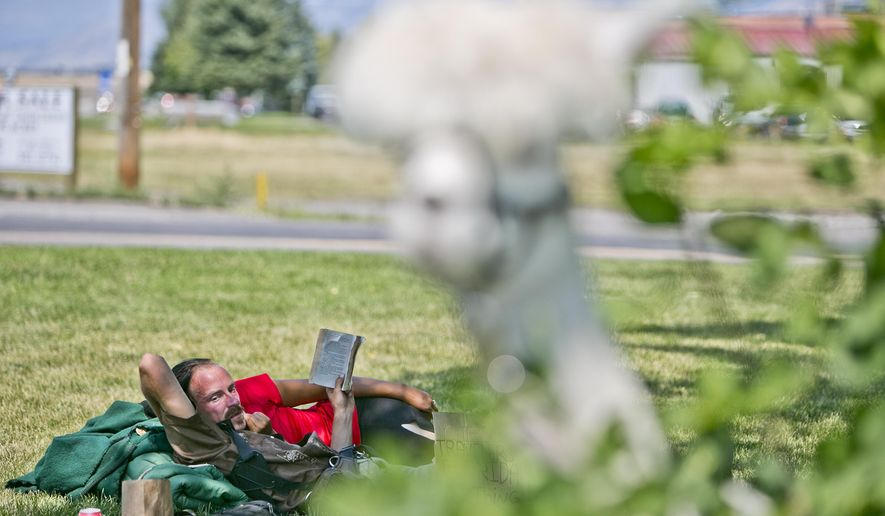 Tinker D'Harra, takes cover in the shade as his alpaca feeds on leaves on Thursday, Aug. 13, 2015, in Bozeman, Mont. D'Harra has been making daily appearances on the local police blotter due to curiosity from passers-by and encounters with concerned residents. (Adrian Sanchez-Gonzalez/Bozeman Daily Chronicle via AP)