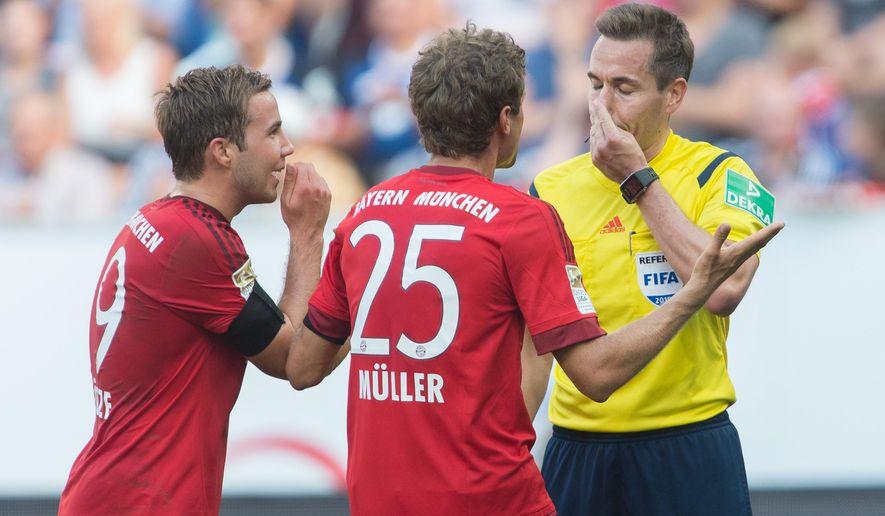 Munich's Mario Goetze, left, and Thomas Mueller  argue with referee Tobias Stieler, right, during the Germany Soccer Bundesliga match between TSG Hoffenheim and Bayern Munich in Sinsheim, southern Germany, Saturday Aug. 22, 2015. (AP Photo/Daniel Maurer)