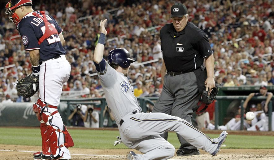 Washington Nationals catcher Jose Lobaton can't handle the throw as Milwaukee Brewers' Scooter Gennett scores, while home plate umpire Joe West watches during the seventh inning of a baseball game at Nationals Park, Friday, Aug. 21, 2015, in Washington. The Brewers won 10-3. (AP Photo/Alex Brandon)