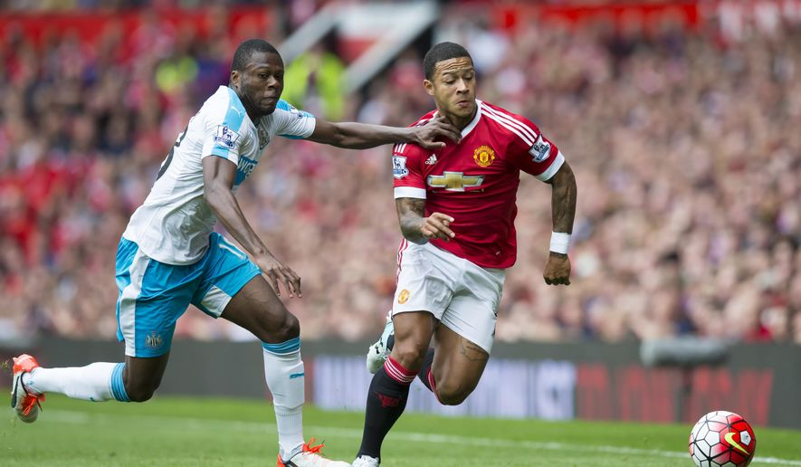 Manchester United's Memphis Depay, centre, fights for the ball against Newcastle's Chancel Mbemba during the English Premier League soccer match between Manchester United and Newcastle at Old Trafford Stadium, Manchester, England, Saturday, Aug. 22, 2015. (AP Photo/Jon Super)