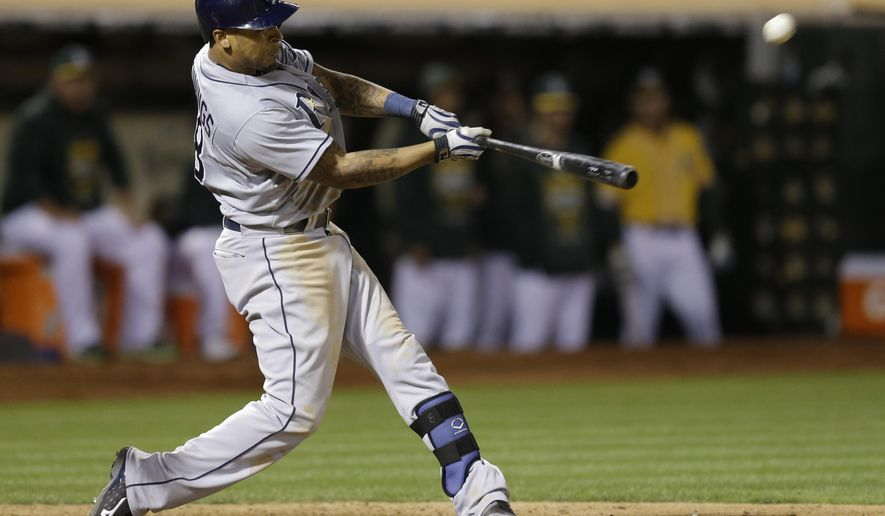 Tampa Bay Rays' Desmond Jennings swings for a home run off Oakland Athletics' Evan Scribner during the ninth inning of a baseball game Friday, Aug. 21, 2015, in Oakland, Calif. (AP Photo/Ben Margot)