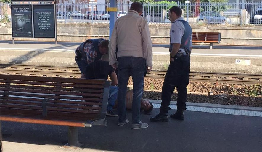In this photo provided by Christina Cathleen Coons, a man is detained on a train platform after an incident on a high-speed train traveling from Amsterdam to Paris, Friday, Aug. 21, 2015, in Arras, northern France. The gunman opened fire on the train wounding several people before American passengers subdued him, according to officials and one of the Americans involved. (Christina Cathleen Coon via AP)