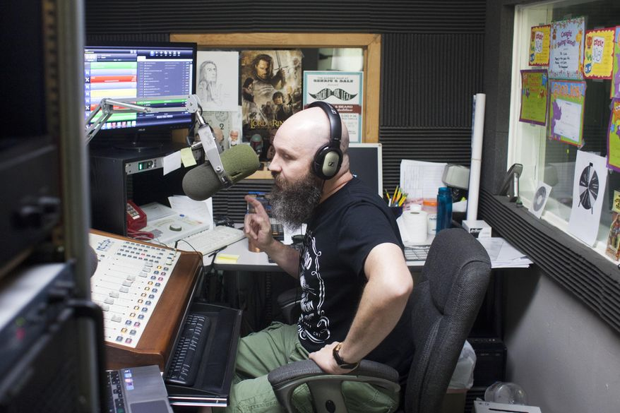 ADVANCE FOR USE SATURDAY, AUG. 22 - In this photo taken, Aug. 12, 2015, J.R. Ramsey, better known as the DJ Dr. Nick Redbone on 103.1 The Edge, works in the recording booth at the Lee Family Broadcasting radio station in Jerome, Idaho. Ramsey said besides having an on-air presence, having an online presence is just as important. That's getting a Facebook page, webpage, Twitter and Instagram accounts, and audio platforms like SoundCloud. (Stephen Reiss/The Times-News via AP) MANDATORY CREDIT