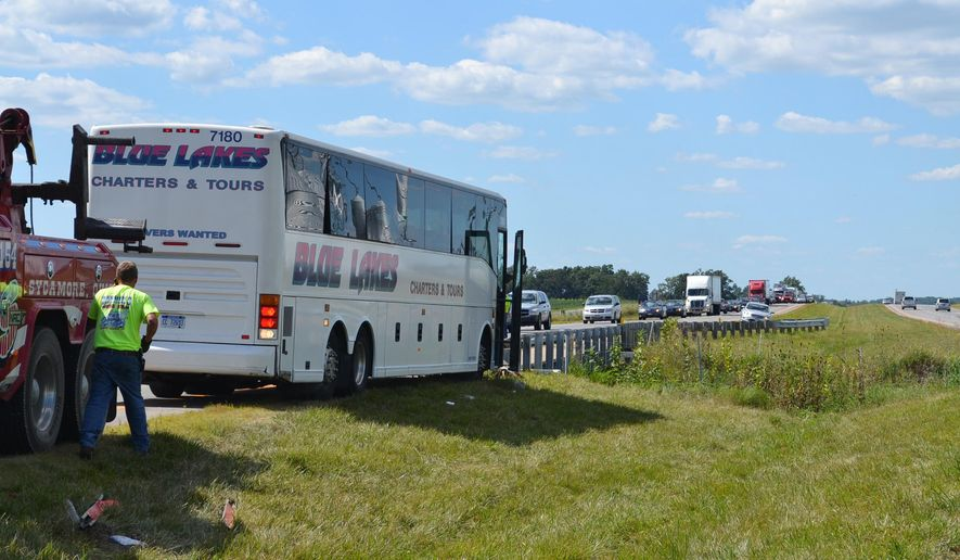 A tow truck driver works to move a crashed charter bus Friday, Aug. 21, 2015, in Pitt Township, Ohio. Authorities say passengers on the packed bus have successfully steered the vehicle away from oncoming traffic in northern Ohio after the driver lost consciousness. (Alissa Paolella/Daily Chief-Union via AP) MANDATORY CREDIT