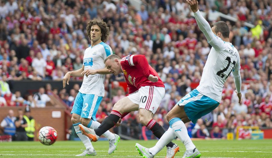 Manchester United's Wayne Rooney, centre, puts the ball in the net only for his goal to be disallowed during the English Premier League soccer match between Manchester United and Newcastle at Old Trafford Stadium, Manchester, England, Saturday, Aug. 22, 2015. (AP Photo/Jon Super)