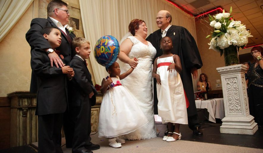 Jayne Rowse, left, and April DeBoer, right, legally marry with their children on stage at the banquet hall in Southfield, Mich. on Saturday, Aug. 22, 2015. The US Supreme Court struck down bans on same-sex marriage nation wide on Friday, June 26, 2015. Judge Bernard Friedman, of U.S. District Court of Eastern Michigan, who overturned Michigan's ban on gay marriage officiated the marriage of the two Hazel Park nurses at the center of the groundbreaking case.  (Kimberly P. Mitchell/Detroit Free Press via AP)