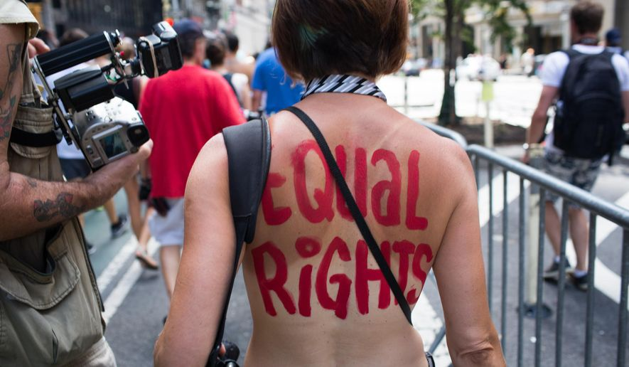 An activist marches in the protest march called the GoTopless Day Parade Sunday, Aug. 23, 2015, in New York. The parade took to the streets to counter critics who are complaining about topless tip-seekers in Times Square. Appearing bare-breasted is legal in New York. But Mayor Bill de Blasio and police Commissioner Bill Bratton say the body-painted women in the square who take photos with tourists are a nuisance. (AP Photo/Kevin Hagen) ** FILE **