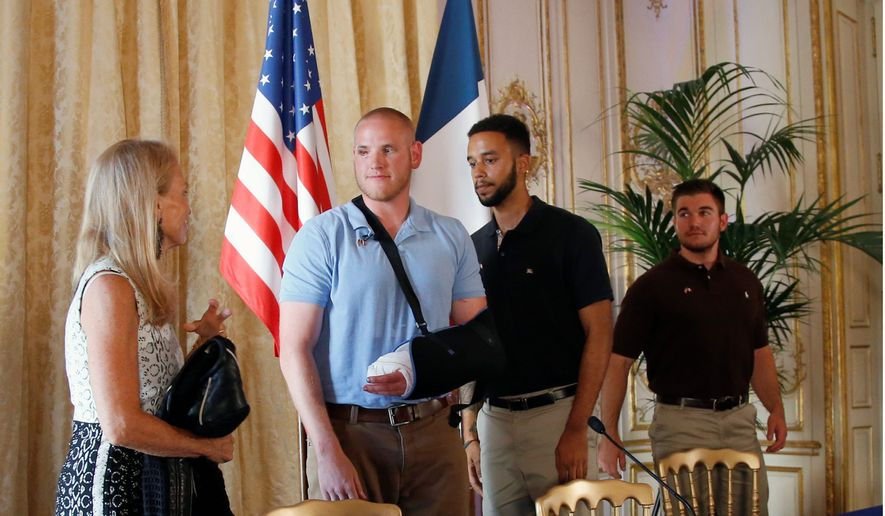 U.S. Ambassador to France Jane D. Hartley (left) met with the three young Americans, two of whom are in the military, who subdued a would-be gunman aboard the Amsterdam-to-Paris train as the man prepared to open fire. The suspect was known to intelligence services in three countries and had ties to radical Islam, authorities said Sunday. (Associated Press)
